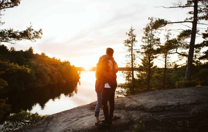 Couple snuggling on the edge of the Canadian Shield as the sunsets over Georgian Bay.