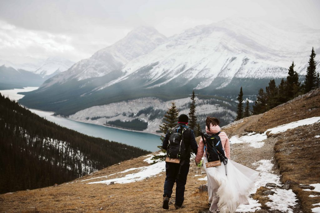 Bride and groom hiking at the summit of a mountain in Kananaskis Canmore area.
