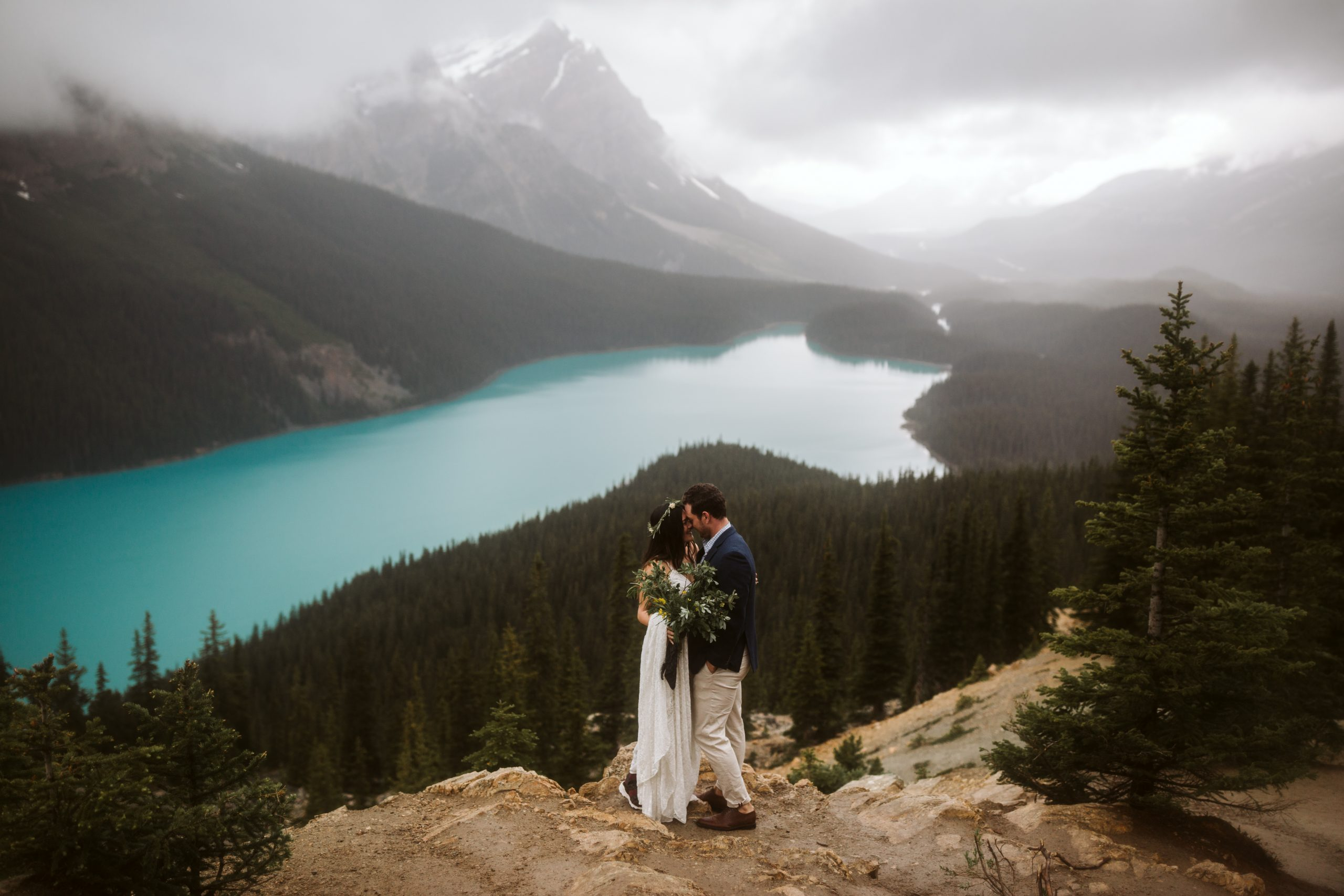 A couple snuggling on the rock bed with Peyto Lake in the background in Banff National Park.