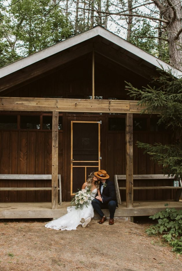 Bride and groom snuggling in front of a cabin at Camp New Moon in Lake of Bays, Ontario.
