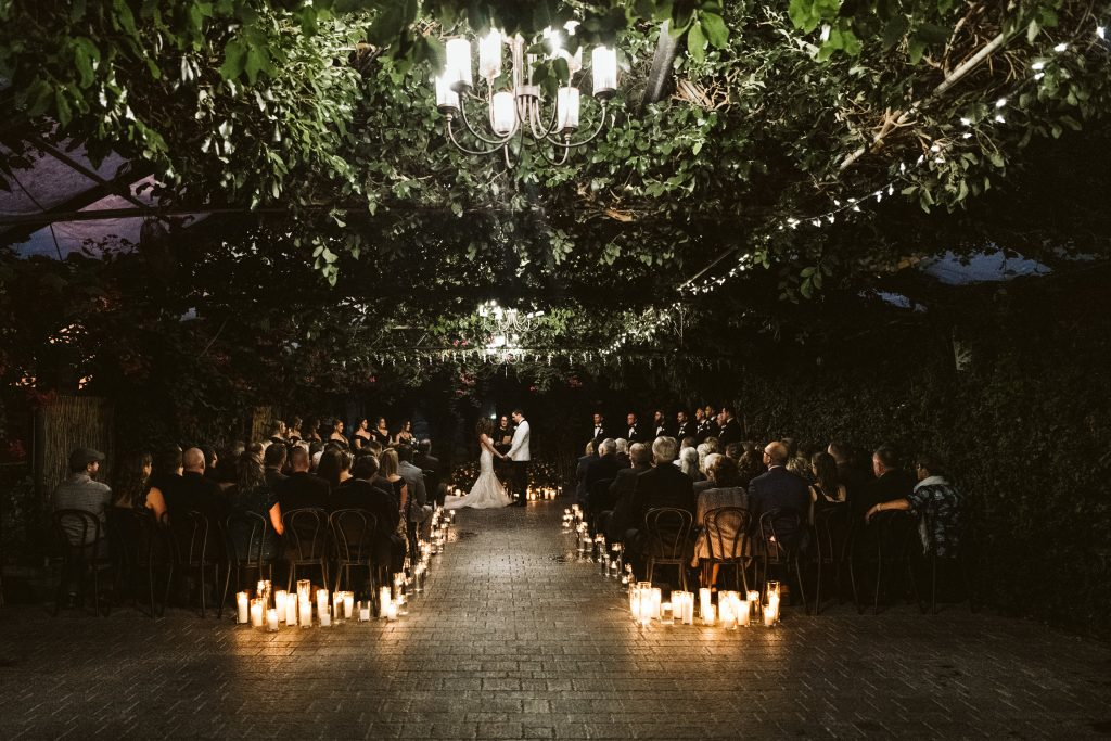 Couple getting married during a candlelit ceremony at Madsens Greenhouse in Newmarket, Ontario