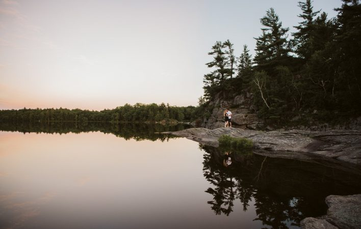 Couple reflecting into the calm waters of Georgian Bay as the sun is setting during the summer in southern Georgian Bay.