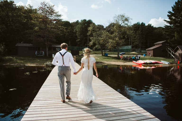 Bride and groom walking down a dock during their muskoka summer camp wedding at Camp Tamarack in Bracebridge, Ontario.