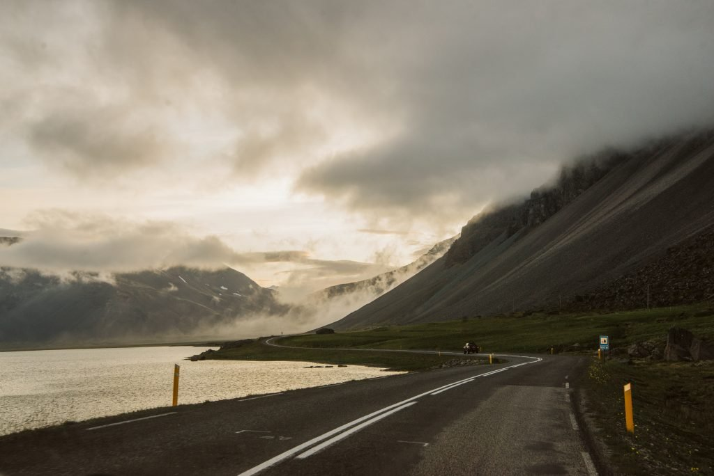 A dark winding road in Eastern Iceland as the midnight sun is setting behind the mountains in Summer.