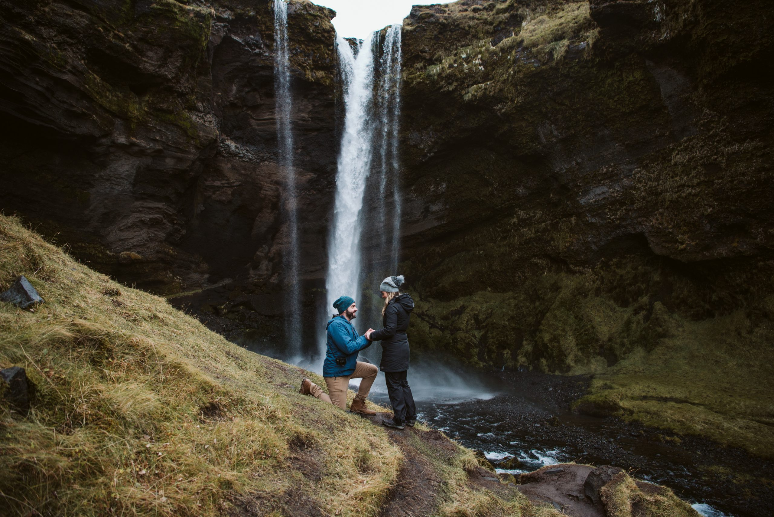 Matt proposing to Jackie at a Secret waterfall during their Iceland Proposal in early winter.